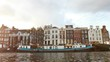 Amsterdam, Netherlands - January 3: Slow motion video of view from the canal to the streets, canals with old flamish houses and bridges in Amsterdam, Netherlands.