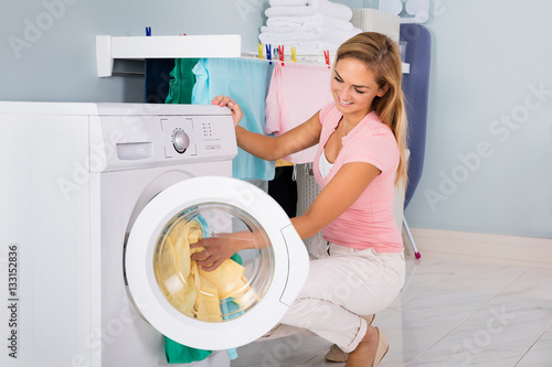 Fotografía  Smiling Woman Putting Clothes In Washing Machine