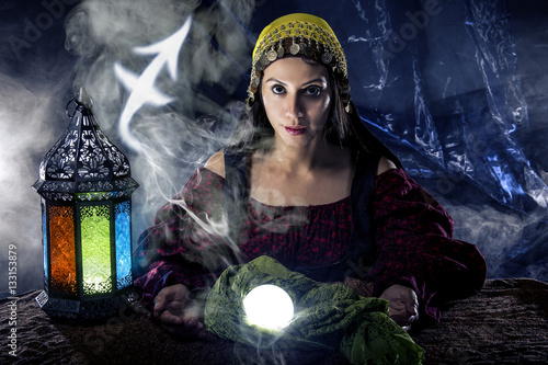 Valokuva  Psychic or fortune teller with crystal ball and horoscope zodiac sign of Sagitar