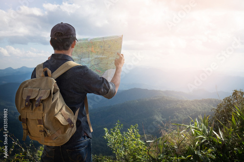 Young Man Traveler with map backpack relaxing outdoor with rocky Wallpaper Mural