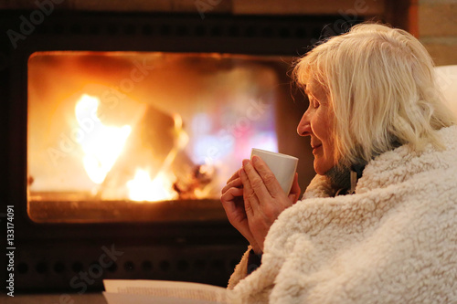 Happy senior woman, wrapped in warm knitted plaid, relaxing