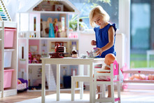Cute Preschooler Girl Having Birthday Tea Party With Her Doll. Little Child Plays In Sunny Room At Home Or Kindergarten. Kids Using Toy Dishes And Cakes.