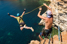 Rope Jumping Off A Cliff With A Rope In The Water. The Ocean. Se