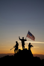 Three Armed Soldiers With The American Flag On The Top Of The Mountain