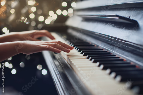 girl playing on an old piano. Beautiful blur background Fotobehang