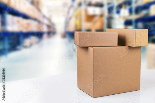 Fotografía  blank cardboard boxes on the table in warehouse with copy space