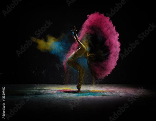 Fotografia Dancer moving in cloud of coloured dust on scene