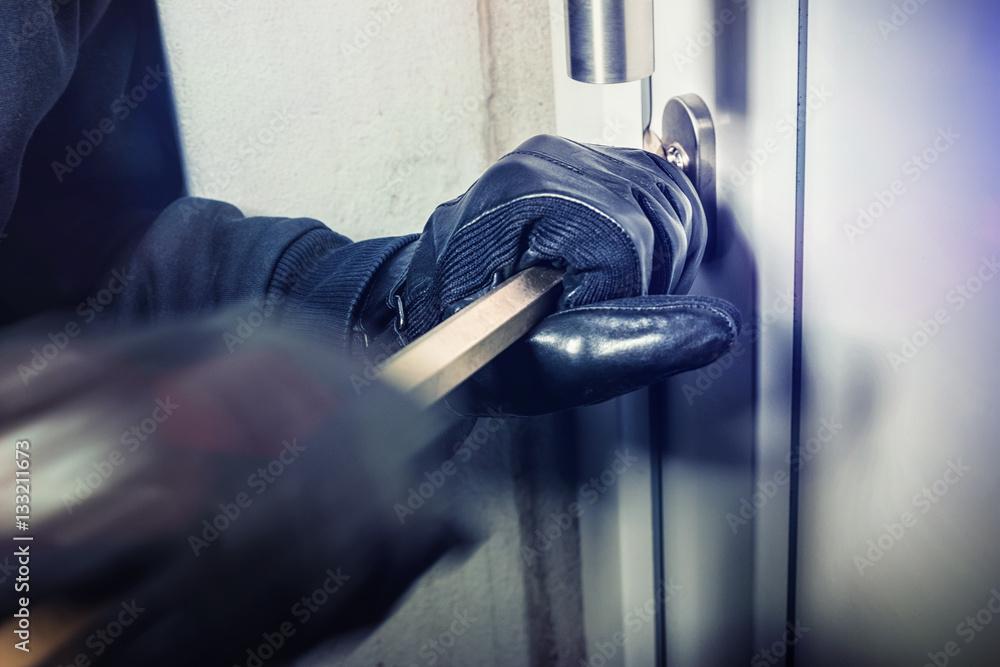 Fototapeta Einbrecher hebeln Fenster / Türe auf und steigen ins haus ein