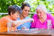 canvas print picture - Seniorinnen spielen Brettspiel mit Altenpflegerin im Altenheim