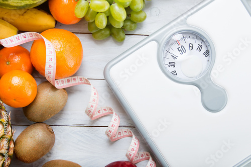 Stack of fruits, white weight scale and tailor meter on wooden board