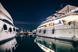 Leinwanddruck Bild - Luxury yachts in La Spezia harbor at night with reflection in wa