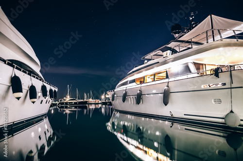 Fototapeta Luxury yachts in La Spezia harbor at night with reflection in wa