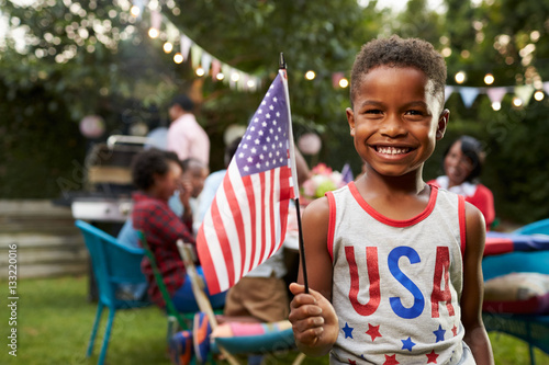 Fotografia  Young black boy holding flag at 4th July family garden party