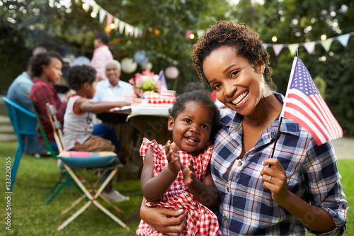 Poster  Black mother and baby hold flag at 4th July party, to camera