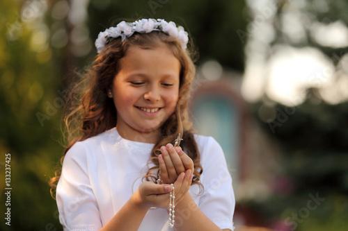 Radosna dziewczynka z różańcem w dłoniach. - fototapety na wymiar