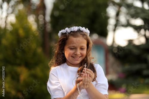 Radosna dziewczynka z różańcem w dłoniach.