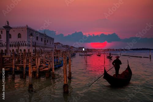 Spoed Foto op Canvas Gondolas Venetian gondolier punting gondola through green canal waters of Venice Italy