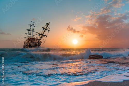 Fotografija  Sailing ship in storm sea against heavy sunset clouds