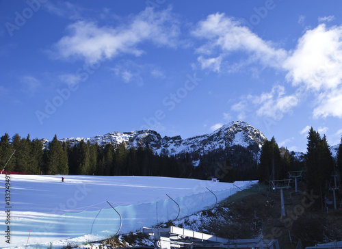 Skiers going down the slope at Aprica Palabione ski route in Italy Wallpaper Mural