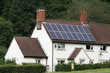 Cottage in countryside with solar panels on the roof.
