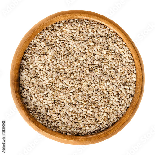 Natural white sesame seeds in wooden bowl. Unpeeled dried fruits of Sesamum, also called benne. Oilseed crops. Isolated macro food photo close up from above on white background.