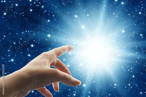 Fotografie, Obraz  woman hand touching a divine light in the universe like a spiritual mystical con