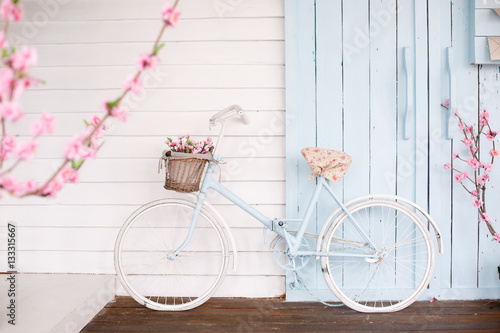 Staande foto Fiets White Bicycle With Beautiful Flower Basket on vintage background. Spring and easter
