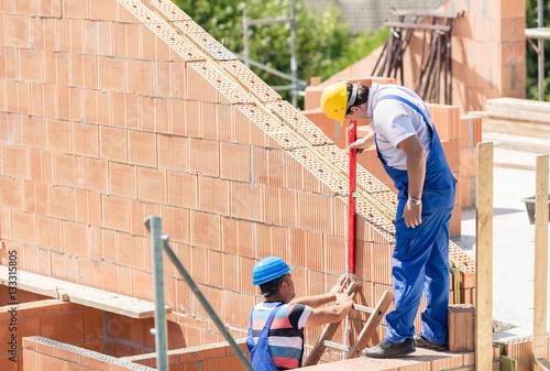 Fotografie, Obraz  Bauarbeiter bauen Haus auf Baustelle
