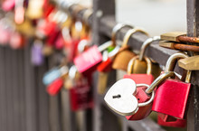 Heart-shaped Padlock Hanging On Rails Among Other Variegated Padlocks