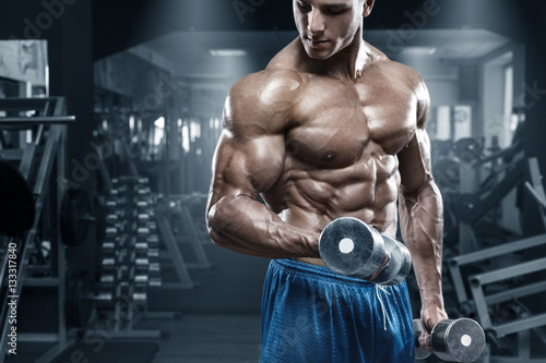 Fotografia  Muscular man working out in gym doing exercises with dumbbells, bodybuilder male
