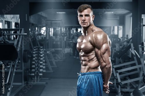 Fotografie, Obraz  Sexy muscular man in gym, shaped abdominal, showing muscles