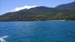 Boat sailing near the Ilha Bela island coast line in Brazil