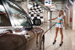 Full length of model with race flag at car wash