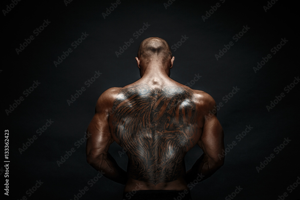 Fototapeta Unrecognizable muscular man with tattoo on back against of black background. Isolated.