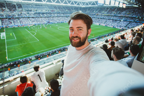 Cuadros en Lienzo Handsome bearded man watching football game and making selfie self-portrait with