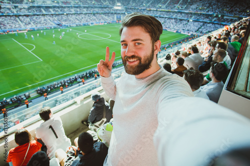 Láminas  Handsome bearded man watching football game and making selfie self-portrait with