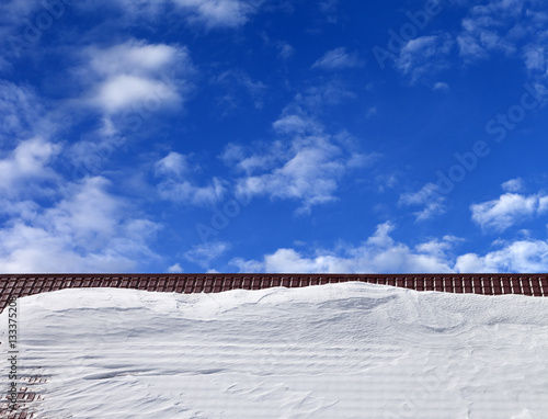 Obraz na plátne Roof in snow and blue sky with clouds