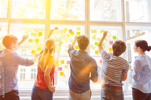 Photo Studenten kleben Zettel mit Notizen an Fenster