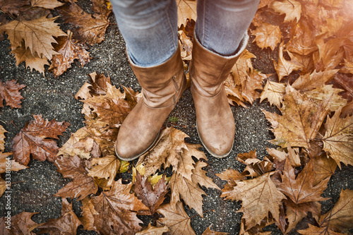 Canvas Prints Countryside Woman's legs in boots on autumn leaves