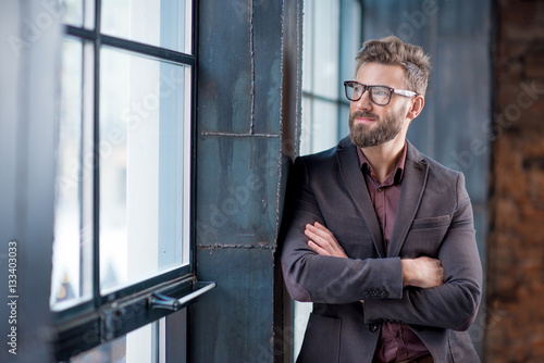 Portrait of caucasian bearded businessman dressed in suit with eyeglasses near window in the loft interior office