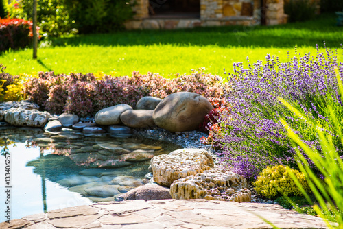 Photo Stands Garden Beautiful backyard landscape design. View of colorful trees and decorative trimmed bushes and rocks