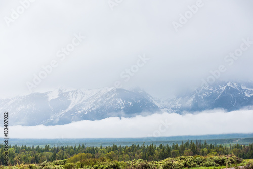 Photo  Grand Teton Mountains covered by large storm cloud casting dark shadow on lake w