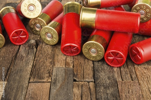 Leinwand Poster 12 gauge red hunting cartridges for shotgun on wooden background