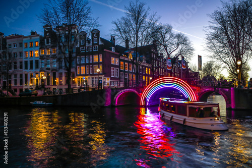 Staande foto Amsterdam AMSTERDAM, NETHERLANDS - JANUARY 10, 2017: Cruise boats rush in night canals. Light installations on night canals of Amsterdam within Light Festival. January 10, 2017 in Amsterdam - Netherland.