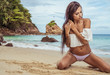 Sensual young brunette beauty wearing white top and bikini bottom with beautiful hair sitting on the beach over beautiful sea, sky and tropical island background