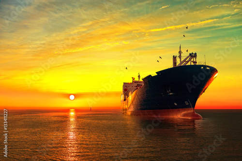 Fotomural  Oil tanker ship at sea on a background of sunset sky.