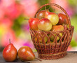 pears in a wicker basket on wooden table with blurred background
