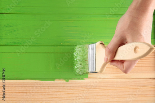 Decorator painting wood with green paint