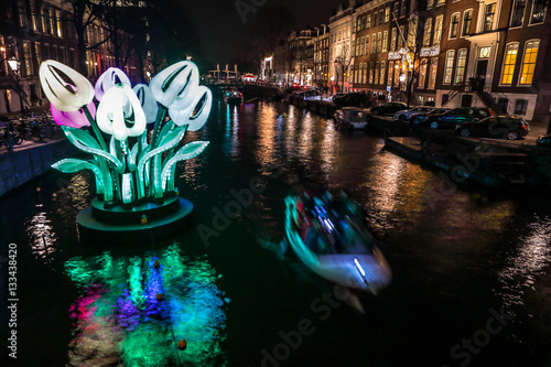 Photo AMSTERDAM, NETHERLANDS - JANUARY 11, 2017: Cruise boats rush in night canals