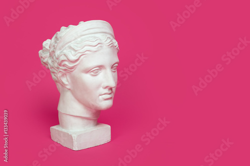 Foto  Marble head of young woman, ancient Greek goddess bust isolated on pink background with space for text